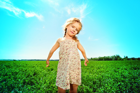 5 year old girl: Pretty little girl on a meadow in summer day. Happy childhood. Blue sky. Stock Photo