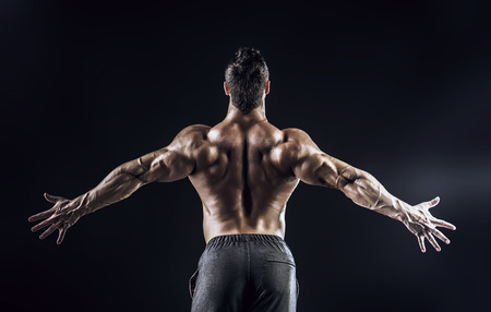 back muscles: Beautiful muscular man bodybuilder posing back over dark background.  Stock Photo