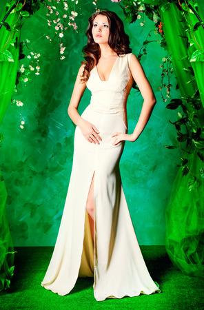 mujer cuerpo completo: Hermosa joven de pie bajo un arco de flores y Loach con mucha vegetación. La primavera y el verano de belleza.