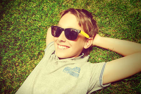 cool boy: Cool boy lying on a grass at a park and smiles. Summer day. Holiday.