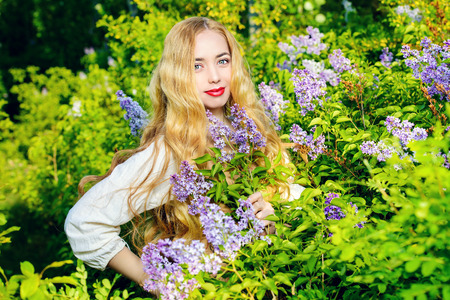 fairy woman: Lovely young woman with magnificent blonde hair near blooming lilac. Countryside.