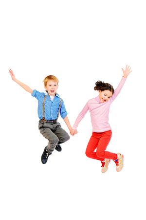 Happy little girl and boy jumping for joy together. Children. Isolated over white. photo