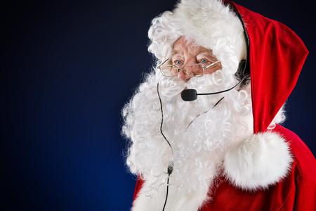 Portrait of a modern Santa Claus in headset. Over dark background.  photo