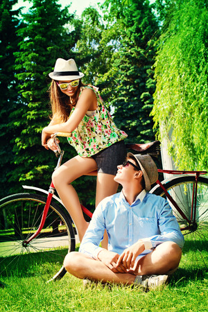 Happy young couple in summer park rides a bike. Romance and love. Stock Photo