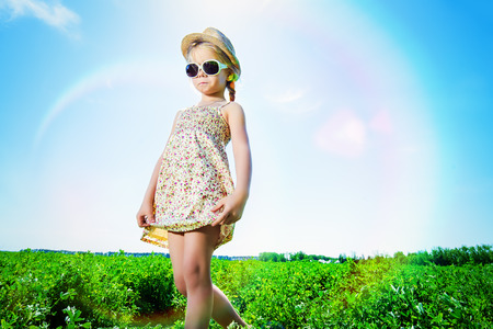 5 year old girl: Cute little girl on a meadow in summer day. Happy childhood. Blue sky.