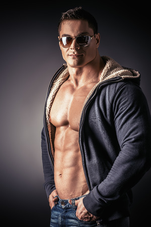Portrait of a sexy muscular young man posing over dark  background. photo