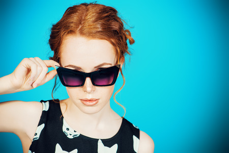 redhaired: Portrait of a pin-up girl wearing stylized sunglasses. Fashion. Retro style.