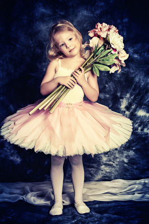 Pretty little girl ballerina in tutu posing over vintage background. photo