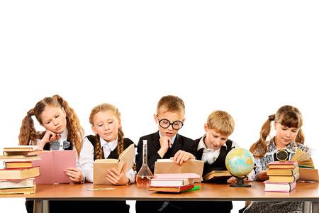 uniform school: Los escolares sentados juntos a la mesa y participado en lecciones. Aislado en blanco.