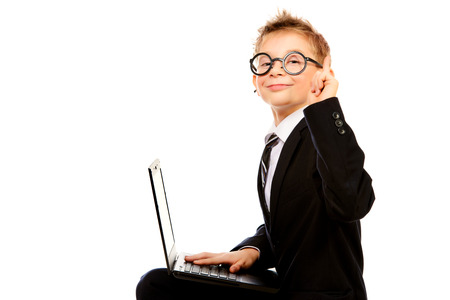 Portrait of a smart boy in a suit and glasses sitting with his laptop. Isolated over white. photo