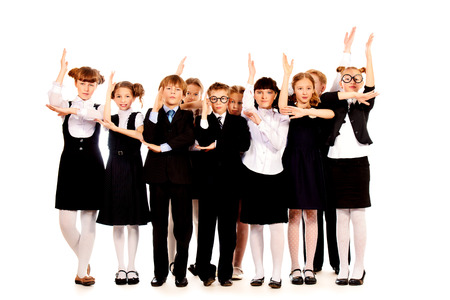 Schoolchildren stand together and raise hands up. Full length portrait. Isolated over white. photo