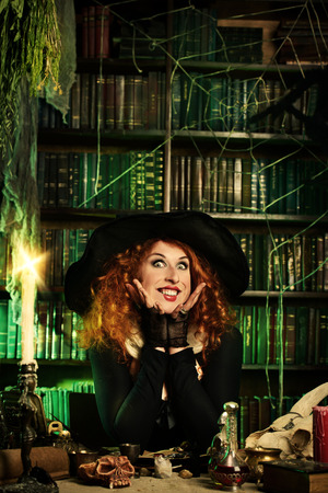 Attractive witch in the wizarding lair. Fairytales. Halloween. photo