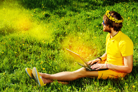 Handsome young man sitting on a grass with his laptop. Summer rest, vacation. photo