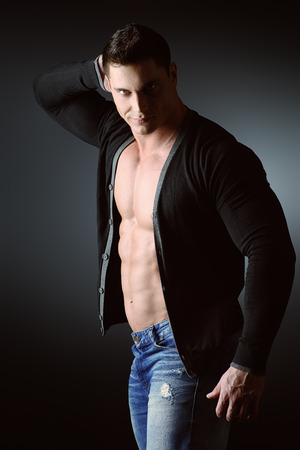 male torso: Portrait of a sexy muscular young man posing over dark  background.