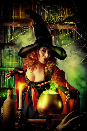 cauldron: Attractive witch in the wizarding lair. Fairytales. Halloween.