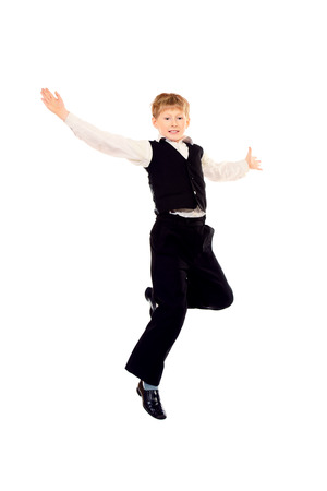 Cheerful ten years schoolboy jumping for joy. Isolated over white. photo