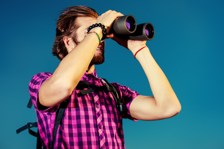 Handsome young man with a backpack looking into the distance with binoculars against blue sky. Active lifestyle, adventure, tourism.  photo