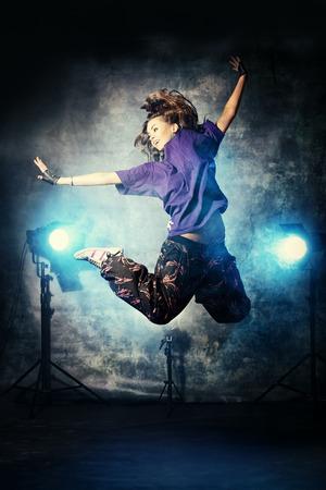 urban dance: Beautiful hip-hop dancer jumping over grunge background.