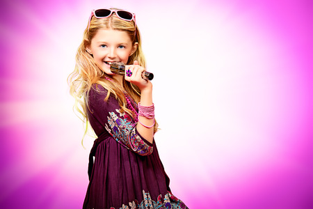 Little modern girl in beautiful dress singing into a microphone over pink background.  photo