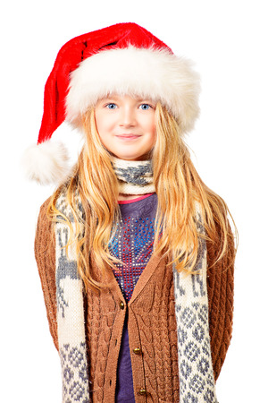 Portrait of a cute ten years girl in red Christmas cap. Isolated over white. photo