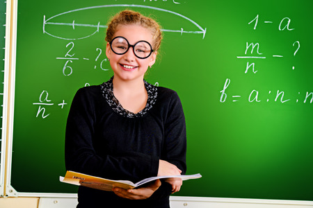 Funny schoolgirl in big round glasses opened the book and looking at the camera. Education. photo
