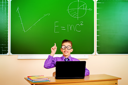 achiever: A schoolboy sitting at a desk in a classroom with a laptop and holds up index finger. Education.