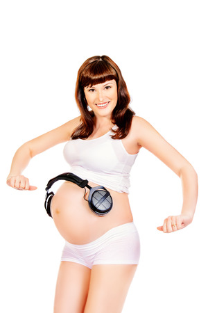 Happy pregnant woman listening to music with headphones. Isolated over white. photo