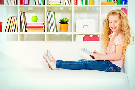 Cheerful little girl sitting on a sofa at home and holds a digital tablet. photo