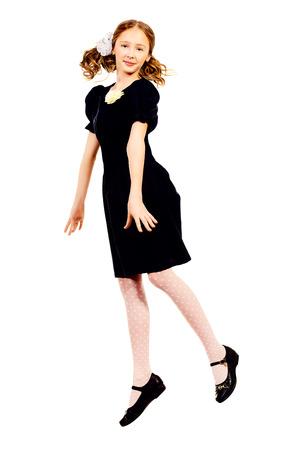 schoolgirl uniform: Happy ten years schoolgirl jumping for joy. Isolated over white. Full length portrait. Stock Photo