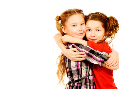 Two smiling girls embracing each other like best friends. Isolated over white. photo