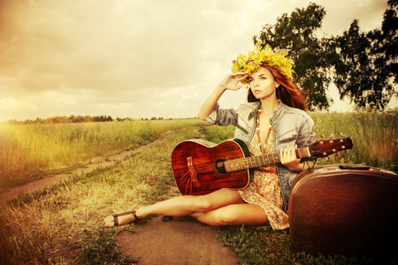 Romantic girl in a wreath of wild flowers travelling with her guitar. Summer. Hippie style.  photo