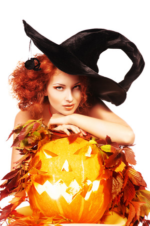 Beautiful red-haired witch casts a spell over pumpkins. Halloween. Isolated over white. photo