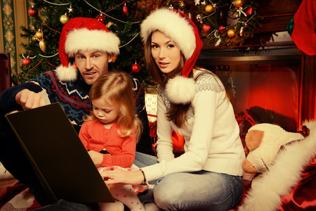 Happy family reading fairy tales at home by the fireplace and the Christmas tree. photo