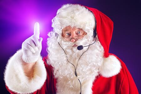 nicholas: Portrait of a modern Santa Claus in headset. Over dark background.
