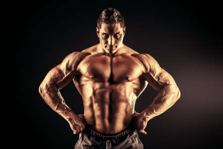 Handsome muscular bodybuilder posing over black background.