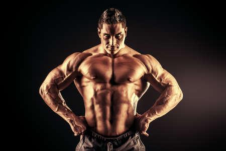 bodybuilder training: Handsome muscular bodybuilder posing over black background.