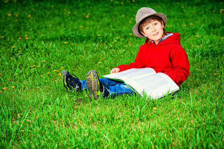 Cute 7 years old boy sitting on a grass with a book. Summer day.  photo