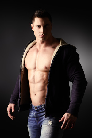 muscle guy: Portrait of a sexy muscular young man posing over dark  background.