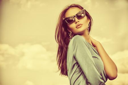 modelos desnudas: Retrato de una dama encantadora en un hermoso vestido elegante y gafas de sol contra el cielo.