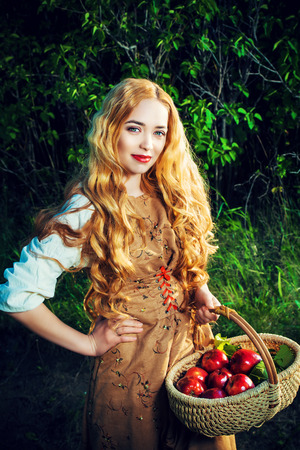 Beautiful young woman with magnificent blonde hair standing outdoor with a basket with apples. Countryside.  photo
