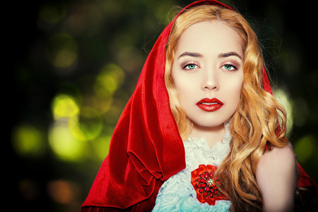 Portrait of a stunning blonde lady in  old-fashioned dress and red cloak in a fairy forest. photo