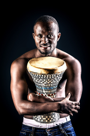traditional culture: African american man posing with his drum. Over black background. Stock Photo