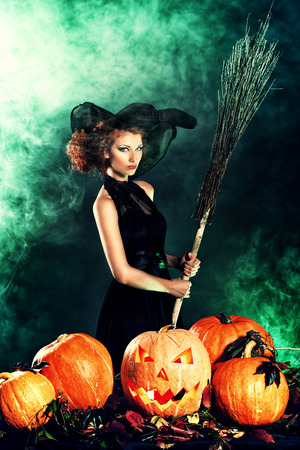 Beautiful red-haired witch casts a spell over pumpkins. Halloween. photo