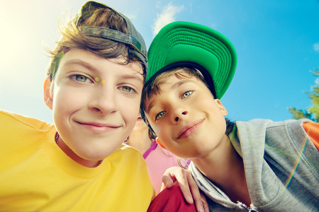 cool kids: Two joyful boys looking at the camera against the blue sky. Summer. Stock Photo