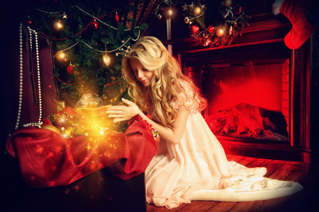 Cute ten years girl sitting at home on a floor near the Christmas tree and fireplace. photo