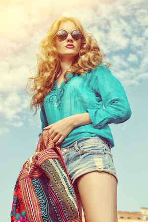 Gorgeous young woman with beautiful wavy hair wearing casual blouse and jeans shorts posing outdoor. Fashion shot. photo