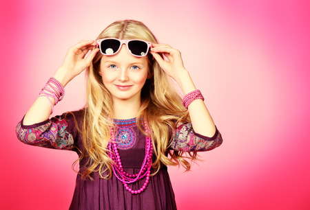 Little fashion girl in beautiful dress, beads and sunglasses posing over pink background.  Stock Photo