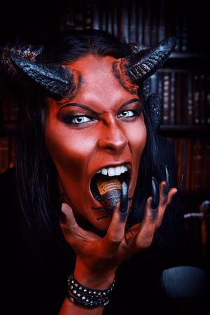 Horned Devil with insects in the mouth. Fantasy. Ancient style. Halloween. photo