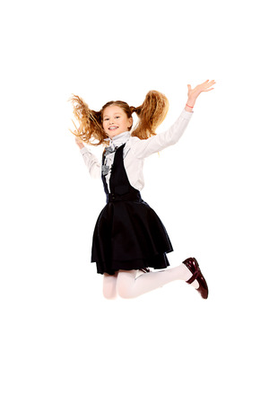 Cheerful ten years girl jumping for joy. Isolated over white. photo