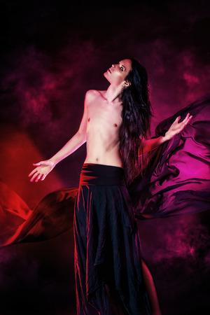 airy: Art photo of a beautiful graceful brunet man dancing with airy black chiffon. Fashion.